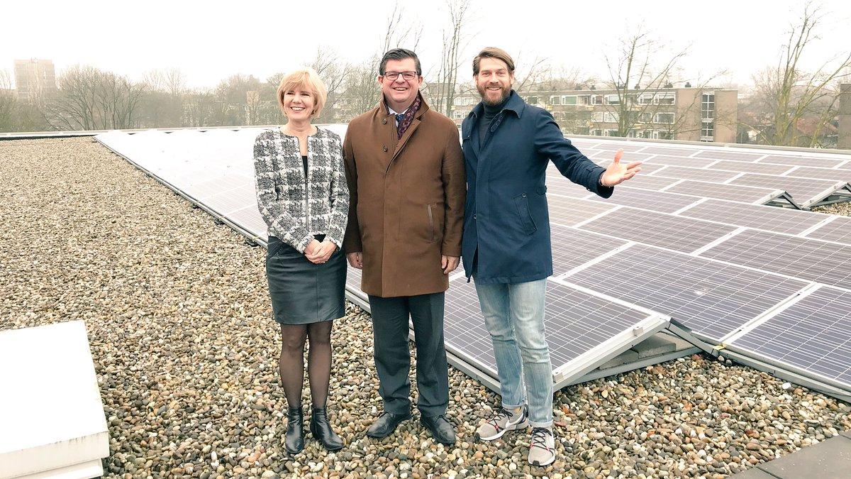 Vlaamse minister Bart Tommelein (midden) op bezoek bij ZonnepanelenDelen, opricher Sven Pluut laat collectief zonnedak Amstelveen College zien